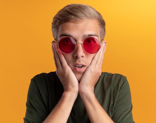 Giovane ragazzo bello sorpreso che indossa la camicia verde con gli occhiali che mette le mani sulle guance isolate sulla parete gialla