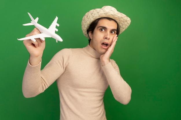 Удивленный молодой красивый парень в шляпе и поднимающий игрушечный самолет, положив руку на щеку, изолированную на зеленой стене