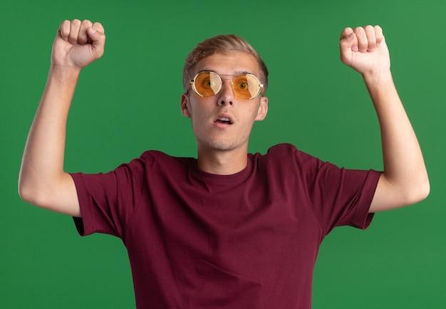 Giovane ragazzo bello sorpreso che indossa la camicia rossa e gli occhiali che solleva le mani isolate sulla parete verde