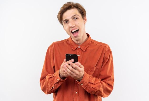 白い壁に分離された電話を保持している赤いシャツを着て驚いた若いハンサムな男