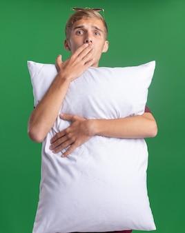 Il giovane ragazzo bello sorpreso che porta la camicia rossa ha abbracciato la bocca coperta del cuscino con la mano isolata sulla parete verde