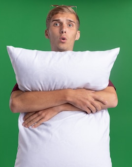 Il giovane ragazzo bello sorpreso che porta la camicia rossa ha abbracciato il cuscino isolato sulla parete verde