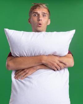 Удивленный молодой красивый парень в красной рубашке обнял подушку, изолированную на зеленой стене