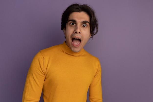 복사 공간이 보라색 벽에 고립 된 노란색 터틀넥 스웨터를 입고 놀란 젊은 잘 생긴 남자