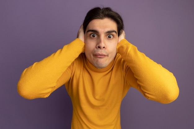 Giovane ragazzo bello sorpreso che indossa maglione dolcevita giallo che mette le mani sulle orecchie isolate sulla parete viola