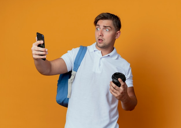 Giovane studente maschio bello sorpreso che porta la tazza di caffè della tenuta della borsa posteriore