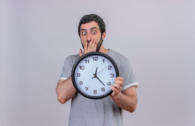 Giovane uomo bello sorpreso che tiene e che guarda l'orologio con la mano sulla bocca isolata sulla parete bianca