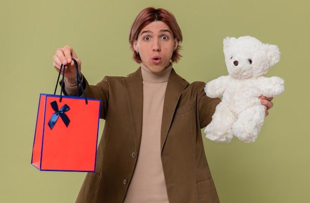 Удивленный молодой красавец, держащий белого плюшевого мишку и подарочный пакет
