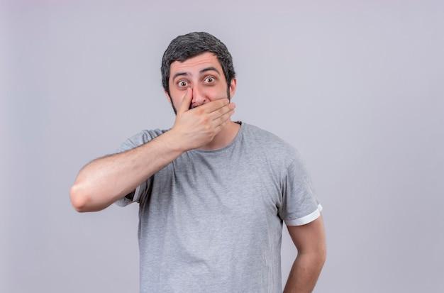 Giovane uomo bello sorpreso che mette la mano sulla bocca isolata sulla parete bianca