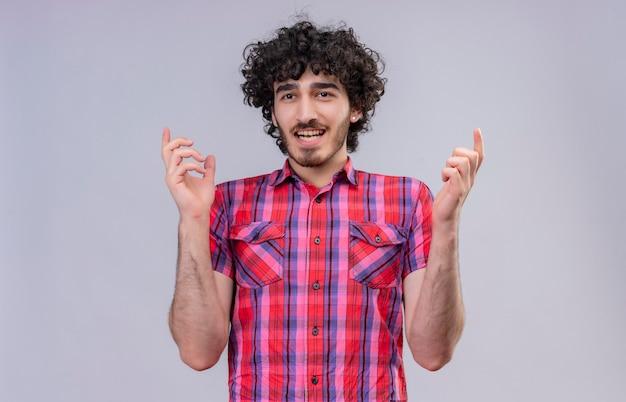 Un bell'uomo giovane sorpreso con i capelli ricci in camicia a quadri alzando le mani e volendo dire qualcosa