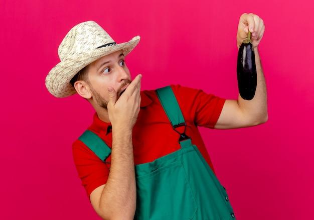 制服を着た若いハンサムなスラブの庭師と帽子を持って、口に手を置いてナスを見て驚いた