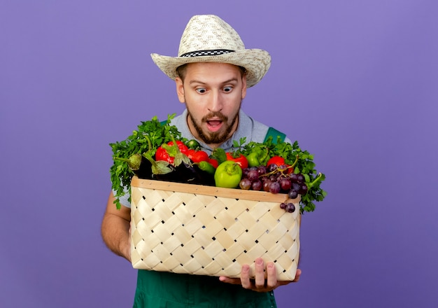 유니폼과 모자를 들고 고립 된 야채 바구니를보고 놀란 젊은 잘 생긴 슬라브 정원사