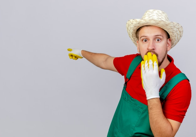 Удивленный молодой красивый славянский садовник в униформе в садовых перчатках и шляпе смотрит, держа руку на рту, указывая за изолированным