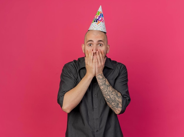 복사 공간이 분홍색 벽에 고립 된 정면을보고 입에 손을 유지 생일 모자를 쓰고 놀란 젊은 잘 생긴 슬라브 파티 남자