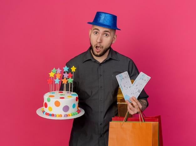 真っ赤な背景で隔離のカメラを見て誕生日ケーキのお金のギフトパックと紙袋を保持しているパーティーハットを身に着けている驚いた若いハンサムなスラブパーティーの男