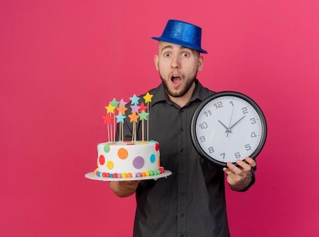 星と時計とコピースペースで深紅色の背景に分離されたカメラを見て誕生日ケーキを保持しているパーティー帽子をかぶって驚いた若いハンサムなスラブパーティー男