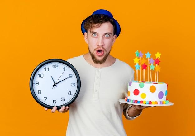 Ragazzo di partito slavo bello giovane sorpreso che indossa il cappello del partito che tiene orologio e torta di compleanno con le stelle che guarda l'obbiettivo isolato su priorità bassa arancione