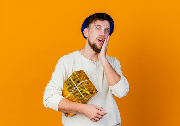 Surprised young handsome slavic party guy wearing party hat holding gift box looking at camera touching face isolated on orange background with copy space
