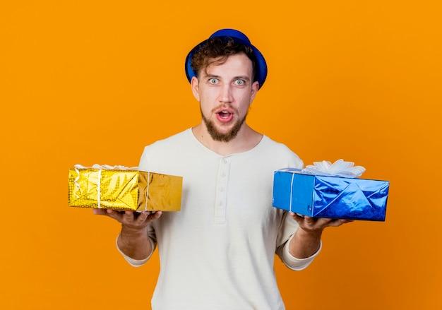 Удивленный молодой красивый славянский тусовщик в шляпе партии, держащий подарочные коробки, смотрящий в камеру, изолированную на оранжевом фоне