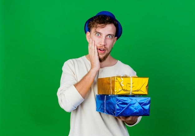 복사 공간이 녹색 배경에 고립 된 얼굴에 손을 유지하는 카메라를보고 선물 상자를 들고 파티 모자를 쓰고 놀란 젊은 잘 생긴 슬라브 파티 남자