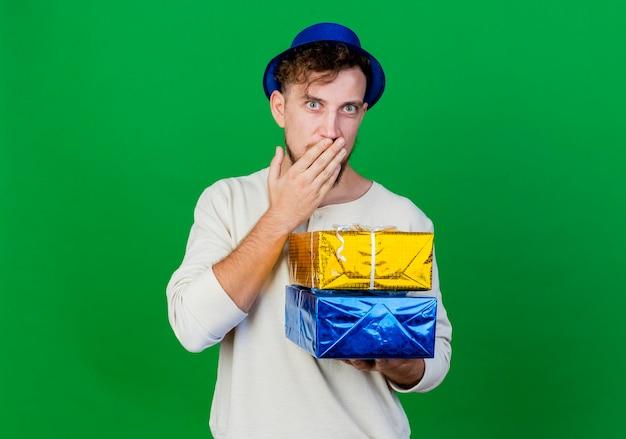 Удивленный молодой красивый славянский тусовщик в партийной шляпе, держащий подарочные коробки, смотрящий вперед и держащий руку во рту, изолированную на зеленой стене с копией пространства