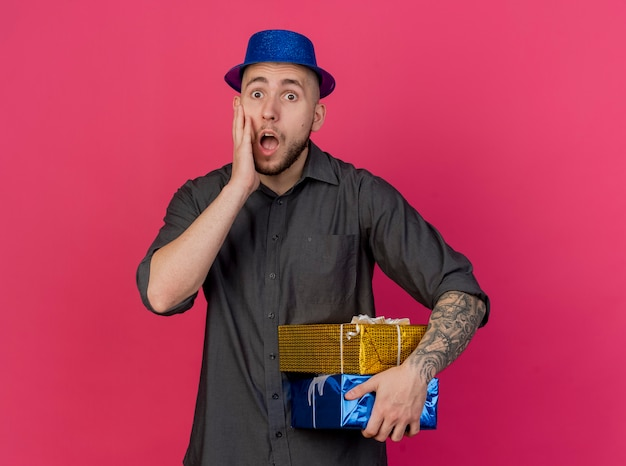 Ragazzo di partito slavo bello giovane sorpreso che indossa il cappello del partito che tiene confezioni regalo tenendo la mano sul viso che guarda l'obbiettivo isolato su priorità bassa cremisi con lo spazio della copia