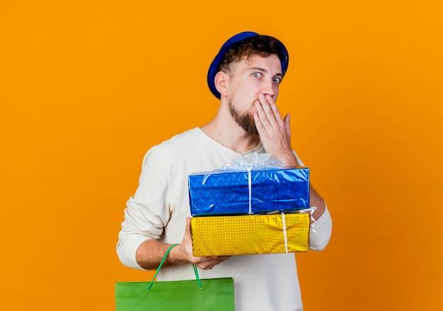 Ragazzo di partito slavo bello giovane sorpreso che indossa il cappello del partito che tiene il sacchetto di carta e scatole regalo tenendo la mano sulla bocca che guarda l'obbiettivo isolato su priorità bassa arancione con lo spazio della copia