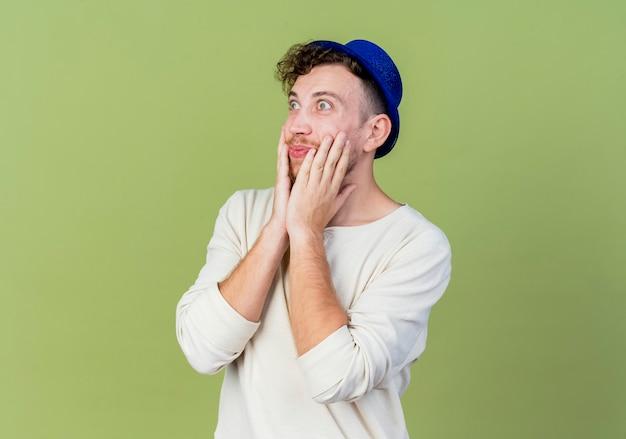Ragazzo di partito slavo bello giovane sorpreso che indossa il cappello del partito che tiene le mani sul viso guardando dritto isolato su sfondo verde oliva con lo spazio della copia