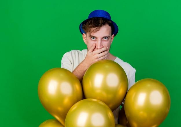 Ragazzo di partito slavo bello giovane sorpreso che indossa il cappello del partito che sta dietro i palloncini che guarda l'obbiettivo che tiene la mano sulla bocca isolata su fondo verde