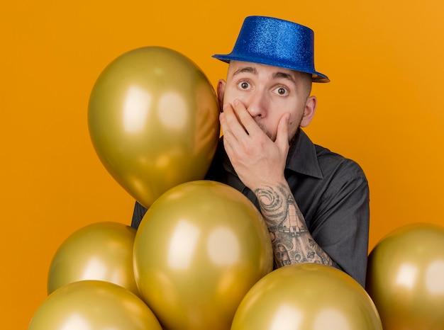 오렌지 배경에 고립 된 카메라를보고 입에 손을 유지 풍선 뒤에 서있는 파티 모자를 쓰고 놀란 젊은 잘 생긴 슬라브 파티 남자
