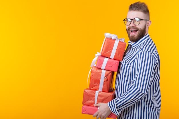 선물 상자의 큰 스택을 들고 안경에 놀란 된 젊은 힙 스터 남자