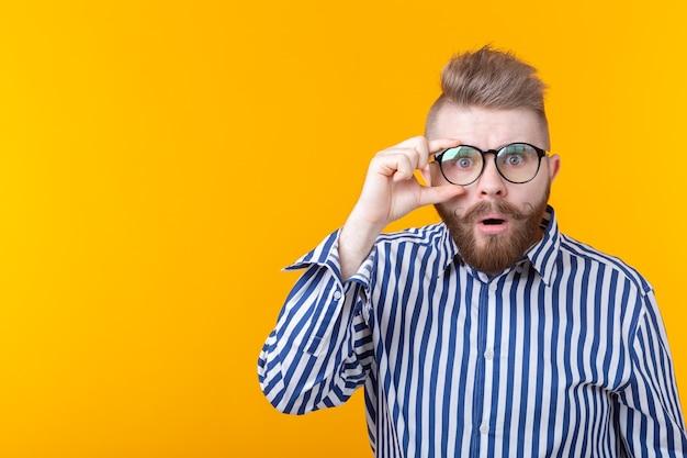 口ひげとあごひげを持つ驚いた若い流行に敏感な男は、黄色のポーズをとって眼鏡を通して見る