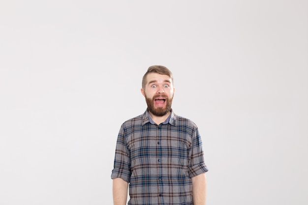 깜짝 찾고 흰색 배경에 포즈 콧수염과 놀란 된 젊은 hipster 남자