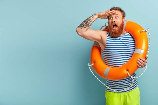 Surprised young holiday maker with red hair and beard, comes on beach with safety equipment as cannot swim