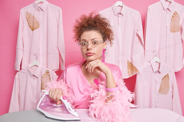 Surprised young housewife keeps hand under chin has combed curly hair wears pink dressing gown uses steam electric iron streams family clothes shocked to have much domestic work. busy housemaid