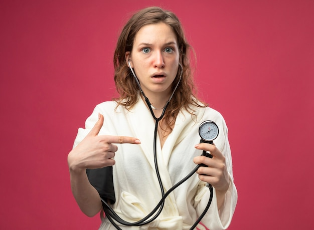 Удивленная молодая больная девушка в белом халате, смотрящая прямо перед собой, измеряет собственное давление с помощью сфигмоманометра, изолированного на розовом