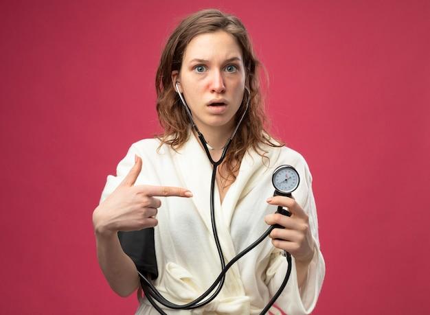 Giovane ragazza malata sorpresa guardando dritto davanti a sé che indossa una veste bianca che misura la propria pressione con sfigmomanometro isolato sul rosa
