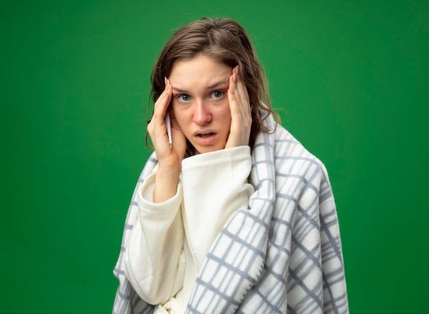 Giovane ragazza malata sorpresa che guarda dritto avanti che indossa una veste bianca avvolta in un plaid mettendo la mano sul tempio isolato sul verde