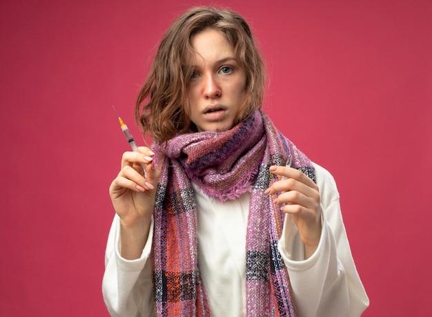 흰색 가운과 분홍색 벽에 고립 된 앰플과 주사기를 들고 스카프를 입고 놀란 어린 아픈 소녀