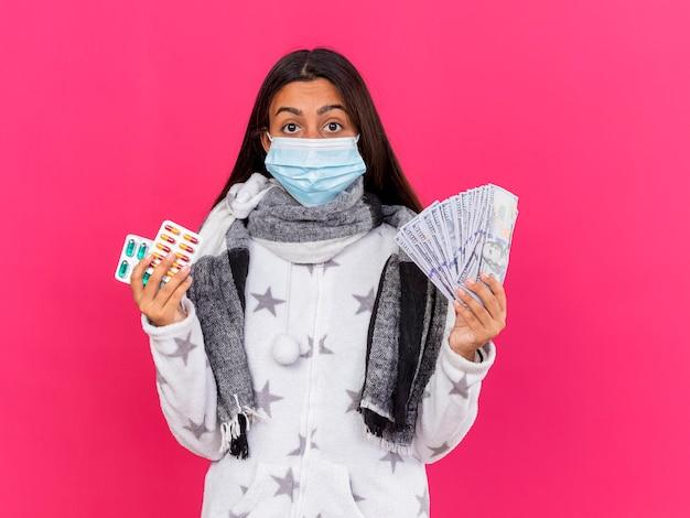 Удивленная молодая больная девушка в медицинской маске с шарфом, держащая таблетки с наличными, изолированными на розовом
