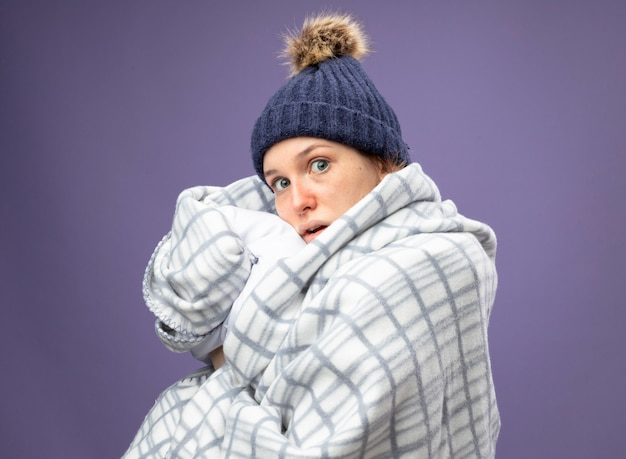 Удивленная молодая больная девушка в белом халате и зимней шапке с шарфом, завернутым в клетчатую подушку, изолированную на фиолетовом