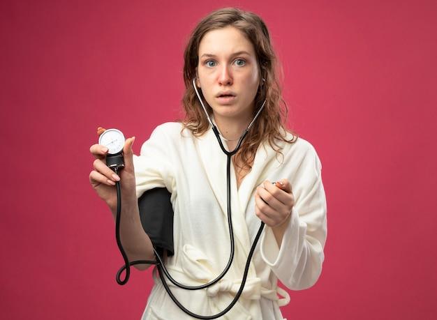 Удивленная молодая больная девушка в белом халате измеряет собственное давление с помощью сфигмоманометра, изолированного на розовом