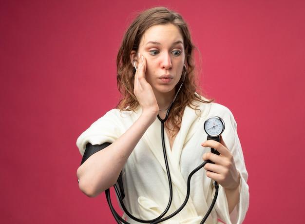 Giovane ragazza malata sorpresa che indossa una veste bianca che misura la propria pressione con lo sfigmomanometro mettendo la mano sulla guancia isolata sul rosa