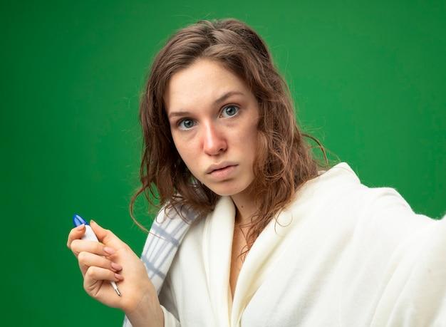 온도계와 녹색에 고립 된 카메라를 들고 격자 무늬에 싸여 흰 가운을 입고 놀란 어린 아픈 소녀