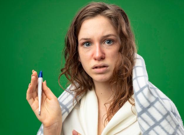 Удивленная молодая больная девушка в белом халате, завернутая в плед, с термометром, изолированным на зеленом