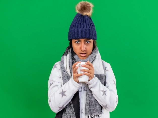 Surprised young ill girl wearing winter hat with scarf holding cup of tea isolated on green background