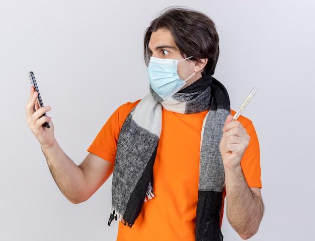 白い背景で隔離の彼の手で電話を見て温度計を保持しているスカーフと医療マスクを身に着けている驚いた若い病気の男