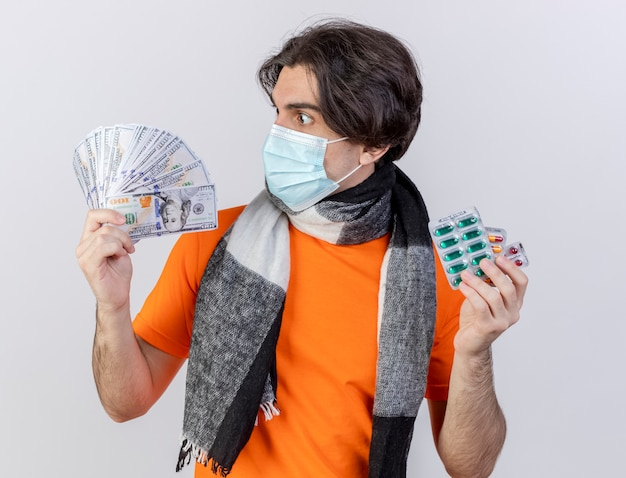 Surprised young ill man wearing scarf and medical mask holding pills and looking at cash in his hand isolated on white