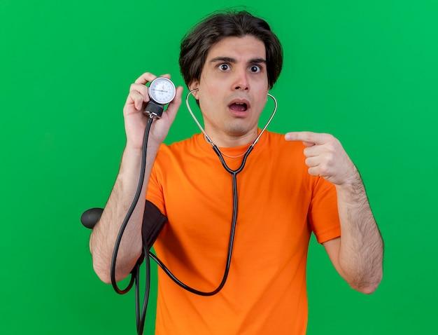 Giovane sorpreso malato che indossa la tenuta dello stetoscopio e indica lo sfigmomanometro isolato su verde