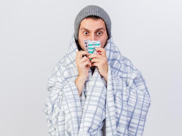겨울 모자와 스카프를 입고 놀란 젊은 아픈 남자는 얼굴 주위에 약을 들고 격자 무늬에 싸여